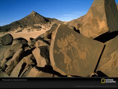 These 2,500-year-old petroglyphs, portraying figures with tulip-shaped heads and hourglass bodies, mark an ancient human presence in the Niger's Sahara Aïr Mountains.