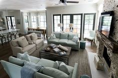 Amazing open plan living room features beadboard ceiling accented with ceiling fan over U shaped sitting area with soft blue slipcovered sofas facing each other across industrial coffee table as well as beige slipcovered armchairs over brown sisal rug.
