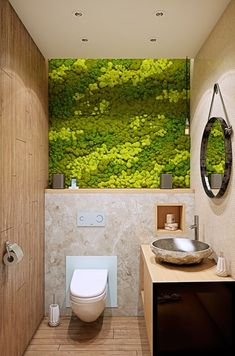 a small powder room is made more eye-catchy with a chic moss wall in several shades