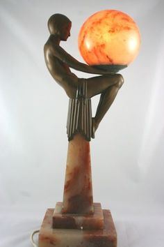 A stunning original Art Deco lamp in the form of a seated nude holding a glowing alabaster ball. The figure is of spelter set onto an alabaster base with the original shade. circa 1930 H 49cm, W at base 15cm