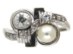 An unusual Art Deco 18ct white gold, natural pearl and diamond ring. It is well designed with the double twist idea incorporating the diamonds and pearl.