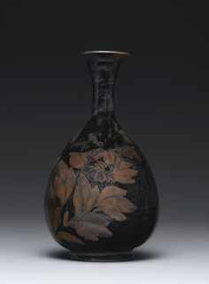 A BLACK-GLAZED RUSSET-SPLASHED VASE (YUHUCHUNPING) NORTHERN SONG / JIN DYNASTY the pear-shaped body rising from a flared foot to a slender neck and everted rim, the lustrous black glaze painted in rust-brown with a stylized floral bloom, the glaze stopping at the foot revealing the buff colored body Height 11 1/8  in., 28.3 cm 5070000