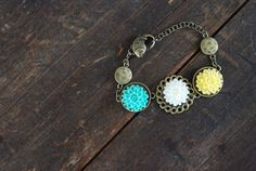 Hooky Bracelet $17 Made with antiqued brass chain and settings adorned with acrylic cabochon flowers. Secure your bracelet with a fish clasp for an added nautical touch.