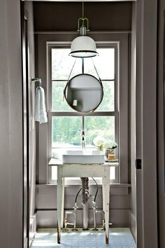 """I embraced the natural light and framed a view by floating a vintage table-turned-vanity in front and hanging a small round mirror over the window,"""" says Paige. """"Dark walls painted Gauntlet Gray by Sherwin-Williams are high contrast and lend interest."""""""