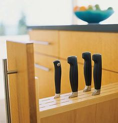 "A narrow pull out for knives between cabinents or ""lost"" space.  If there's enough space under them, could store cutting boards there as well.  (Would have to reconsider for kitchen with small children)"
