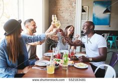 Happy group of diverse male and female young adults in casual clothing toasting drinks together at table in restaurant