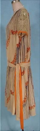 c. 1926 Deco Tea-colored and Orange Design Crepe Day Dress.Tea colored thin silk crepe fabric in two layers. The under sheath which you see in the front panel, hemmed with wide lace, and then the attached overdress, pleated from the shoulders, edged in wide ecru lace which is totally open front and back and only ties down with the separate original tie belt. The design is a print in the silk fabric. Black stripes ending in orange flowers in the deco design. Sideway