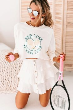"""Make Sporty Look Cute With This Bone """"New York Tennis Club"""" Cropped Graphic Top! The Flowy Fit & Cropped Length Make This Top Perfect To Wear With All Your Favorite Denim Or Loungewear! $27, FAST AND FREE US SHIPPING! Flying Monkey Jeans, Tennis Clubs, Ruffle Shorts, Juniors Jeans, Sporty Look, Loungewear, Casual Tops, Sexy Women, Street Wear"""