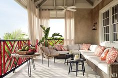 The veranda of designer Alessandra Branca's Harbour Island, Bahamas, home is furnished with a vintage French rattan chair and an RH sectional sofa.