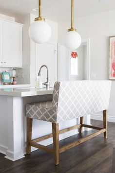 A cozy booth beats out stools any day. Fake a snug nook in the middle of the room by pulling up a plush island-height bench. Sunday brunch just got so much better.    Shop a similar look: custom bench, pindler.com