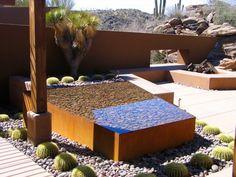 jardin contemporain aménagé avec une clôture acier Corten et un bassin de jardin surélevé en acier Corten