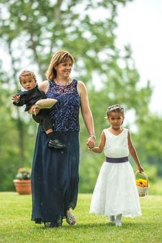 mother of the bride walks flowergirl and ringbearer down the isle