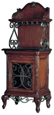 """Wine Curio    Crystal goblets will dangle from the upper shelf while the cabs and zins are stowed properly beneath. Ornamental iron scrollwork graces a richly hand rubbed cabinet with inlaid fossile stone counter and pull-out drawers and serving board. 28x20x72""""."""