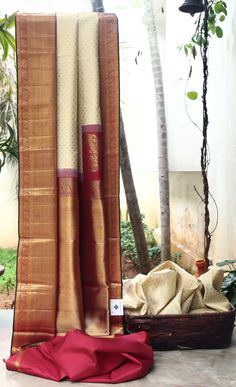 ELEGANT OFF WHITE WITH GOLD ZARI BUTTAS ALL OVER HAS CLASSIC MAROON WITH GOLD BORDER AND PALLU GIVING THE SAREE OPULENT FINISH. THE DARK GREEN SHOT MAROON SELVEDGE ADDS BEAUTY TO THE SAREE