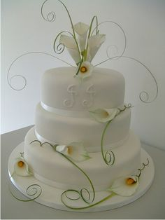 Beautiful white cake with calla lilies and white ribbon.  ᘡղᘠ