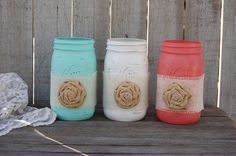 3 quart size mason jars. Hand painted in mint green, coral and white, with a ribbon of white burlap and a burlap flower, lightly distressed with a protective coating. They are not painted on the insid