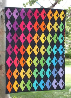 """This pattern is our new fresh take on our popular Diamond Alley quilt pattern. Show off your favorite prints, create a cascade of color or feature a single print as the background. The pattern included three sizes: Tall (33"""" x 45""""), Grande (58"""" x 77"""") and Venti (84"""" x 99""""). The pattern is fat-quarter or 10"""" square precut friendly.  You will need a 60 degree Triangle Ruler to make this quilt! Find themhere."""