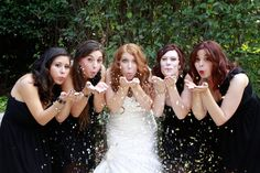 Bride and Bridesmaids Blowing Confetti Glitter into the Camera.  Photo By Christina Lorraine Photography