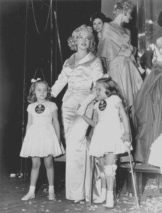 """1958 / Marilyn participe au show de mode annuel """"March of Dimes"""", qui se déroulait au """"Waldrof-Astoria"""" de New York le 28 janvier 1958, accompagnant les jumelles de 6 ans Lindy et Sandy Sue SALOMON. Les bénéfices de ce show sont reversés à la recherche de vaccination de la polio. Marilyn porte un ensemble veste et jupe longue de couleur champagne en soie et satin, et dont la veste fut conçue par John MOORE pour """"Talmack"""". Les participants au show étaient composés des membres du groupe de…"""