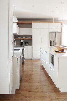 Cuisine blanche avec insertion de bois, de style contemporaine, plancher de bois, dosseret de céramique carrée grise, micro-onde dissimulé dans l'ilot, comptoirs de quartz blanc