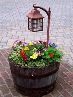 wine barrel with flowers and a lantern - great for a patio