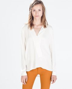 I like the cut of this blouse, but I don't like the cream color or gold buttons on the sleeves.