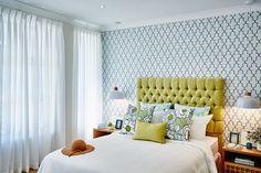 Ta eklektyczna sypialnia łączy w sobie styl glamour ze skandynawskim. Tapeta w koniczynę znalazła się tylko na ścianie za łóżkiem. Stanowi ona wdzięczne tło dla pikowanego zagłówka łóżka w musztardowym odcieniu.
