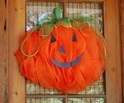Pumpkin Door Decoration with face made with deco mesh and a work wreath.  Great blog!
