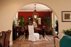 A graceful arch perfectly frames the rich red wall, rustic light fixture and mirror in this dining room from Pardee Homes, San Diego. The angled white chair invites the viewer in. Dining Room Colour Schemes, Dining Room Colors, Dining Rooms, Color Schemes, Pardee Homes, Green Dining Room, Red Home Decor, Interior Decorating, Interior Design