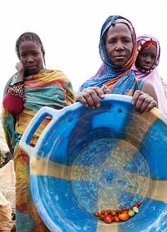 Women show their small harvest. Photo credit: David Orme.