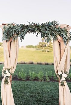 A classic fabric-draped arch topped with lush eucalyptus leaves and soft white peony arrangements | Brides.com