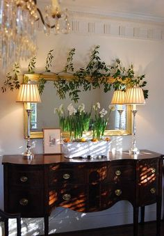 .The striking contrast of mahogany and light painted wall, the golden framed horizontal mirror with side lamps, and the addition of greenery make an airy and inviting combination.