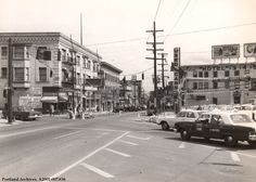 W Burnside Street, 1967.  W Burnside Street looking east from SW 18th Ave. The building on the left side of the image is still standing. There are several business that are visible, including Derby Cleaners and Ace Hotel.