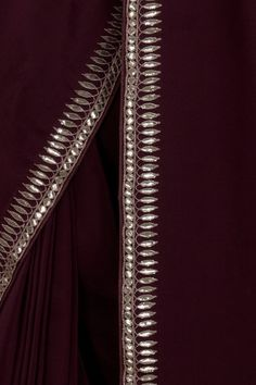 From our Wedding and Bridal Collection, this is a Burgundy pure crepe saree and blouse with intricate exquisite silvery gold gota patti hand embroidery. The embroidered work adorns the saree borders inches wide. The blouse is adorned with al Saree Blouse Neck Designs, Fancy Blouse Designs, Saree Blouse Patterns, Hand Embroidery Dress, Hand Embroidery Designs, Gota Patti Saree, Drape Sarees, Stylish Work Outfits, Simple Sarees