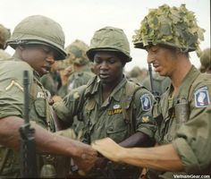 """Members of Company B, 2nd Battalion, 173rd Airborne prepare for the first major ground combat operation by U.S. forces of the Vietnam War.     Together with Australian and ARVN troops, the 173rd undertake a search and destroy mission in War Zone """"D"""", north west of Saigon (III Corps).    The solider on the right has woven strips of camouflage parachute silk into net to break up the outline of his helmet.    Photo taken: June 1965"""
