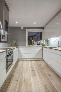 Witte keukenmeubelen, natuurlijke hout en een sober witte raam geven aan dit keuken een warme modern stijl.