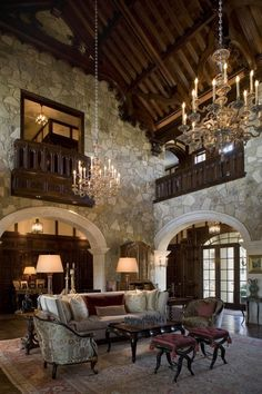 A breathtaking living room, done in a formal Tudor style, with a steeply pitched vaulted wood ceiling and rustic stone walls  (via Interior Designer -Mark Cravotta)
