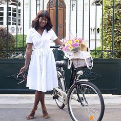 A white shirtdress and colorful bouquet are bike-riding essentials for Angélique of The Fashion Everyday.
