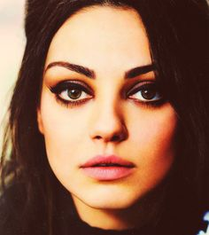 Mila Kunis New makeup inspiration...hmm, let's see, a few coats of mascara, eyeliner smudged all to hell, what looks like deep burgundy/purple eyeshadow? Goes great with her green/hazel eyes. Some soft pink lipstick with blue undertones to top it all off. Gorgeous.