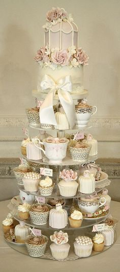 Teacup themed wedding cake tower featuring cupcakes with flower and pearls accents in a palette of gold, pink and ivory.