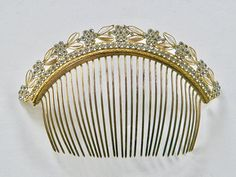 An antique French Empire diadème, of glass pearl navettes and clear pastes, arranged in a floral decoration on a gilt frame. An embossed floral design decorates the bridge of the frame. CONDITION: Excellent. No missing, cracked, or broken stones or pastes; bright pastes and gilt, including on the teeth; no bends or repairs. There looks like a tiny partial crack on the bridge of the teeth, which does not affect the tiara, nor the integrity of the piece. MEASURES: 6.5 x 4.12 in / 16.5 x 10...