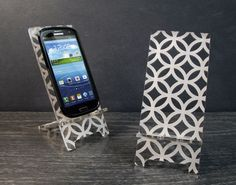 Pretty phone stands from Phonetastique on Etsy - laser etched acrylic. Nice, low-tech solution for a desk or nightstand.