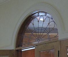 Arched leaded glass window. Transom window over wood doors ...
