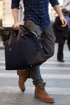 Shop this look on Lookastic:  http://lookastic.com/men/looks/grey-dress-pants-and-brown-boots-and-navy-duffle-bag-and-navy-longsleeve-shirt/1708  — Grey Wool Dress Pants  — Brown Suede Boots  — Navy Canvas Duffle Bag  — Navy Plaid Long Sleeve Shirt
