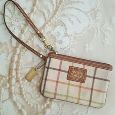 """{Coach} Cream Tattersall Wristlet NEW LISTINGAuthentic Coach wristlet. Cream Tattersall print with tan leather trim. Great pre loved condition. Slight wear on the gold hardware and color change on the outside. No stains, rips, or tears. Beautiful blue lining on the inside with no wear whatsoever. Measurements: 6""""L x 4""""H. Please keep in mind Poshmark takes 20%. Coach Bags Clutches & Wristlets"""