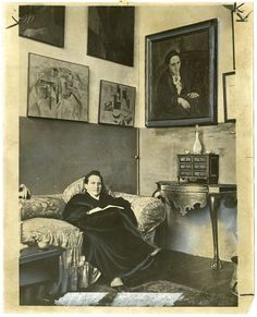 Gertrude Stein sitting on a sofa in her Paris studio, with a portrait of her by Pablo Picasso, and other modern art paintings hanging on the wall behind her.