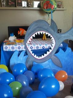 Fun Photo Booth idea - take pics with kids heads in shark's mouth. Hang a blue tablecloth as a backdrop....great for kids nautical, under the sea, Nemo or shark party! Send to guests later with thank you cards.