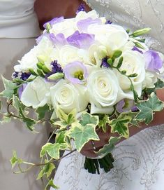 A simple fragrant bridal posy of 'Boeing' roses, scented freesias, purple lisianthus, lavender with pretty trailing ivy creating an informal pretty feel for this lovely wedding bouquet..