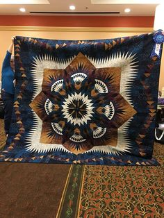"Prairie Star, designed by Quiltworx.com, made by Kay Woody. Made for her son Walter, ""Walter's Prairie Star"" took Best of Show at the Lee's Summit Quilters' Guild quilt show. A flying geese border was added to enlarge the quilt to a king size."