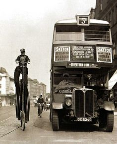 Karl Sander, a former German circus performer, demostrates his novel way of advertising as he rides besides a bus in Streatham in south London, 9 August 1932.